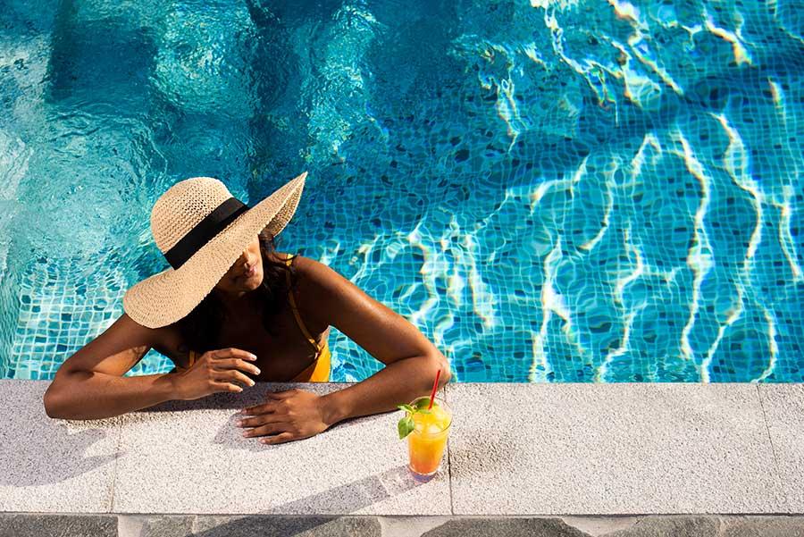 Bildmanér för Pool Store, kvinna med solhatt i poolen