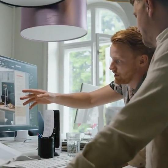 Två män pekar på en datorskärm och resonerar.